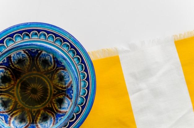 Голубая чашка травяного чая и блюдце на скатерть на белом фоне Бесплатные Фотографии