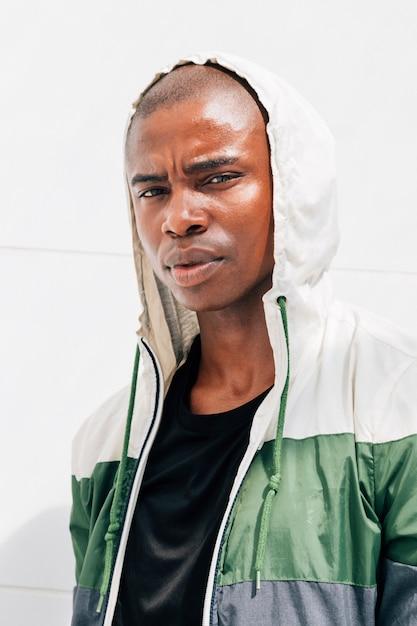 カメラ目線の白い壁に対してパーカー立っている若いオスの運動選手の肖像画 無料写真