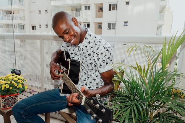 ギターを楽しむバルコニーの椅子に座っているアフリカの笑みを浮かべて若い男 無料写真