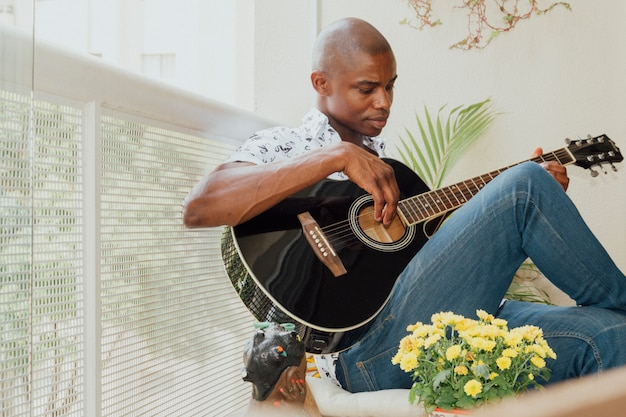バルコニーでギターを弾くアフリカの若い男のクローズアップ 無料写真