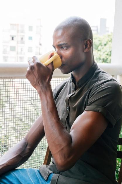 バルコニーに座ってコーヒーを飲みながら筋肉の若いアフリカ人のクローズアップ 無料写真