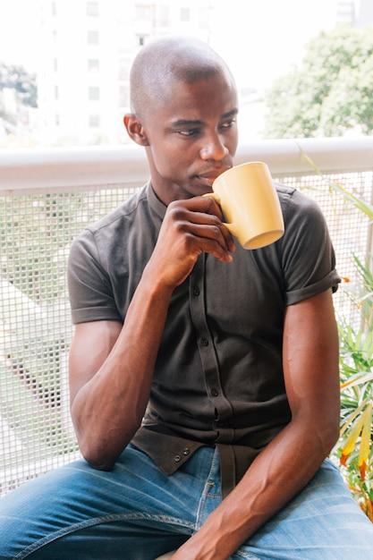 バルコニーでコーヒーを飲みながらアフリカの若い男の肖像 無料写真