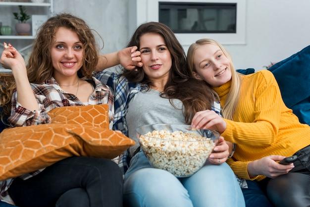 ポップコーンを食べながら映画を見ている友人 無料写真