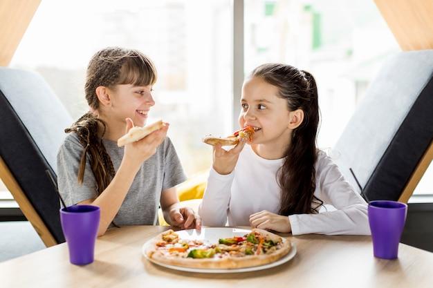 Девочки едят пиццу Бесплатные Фотографии