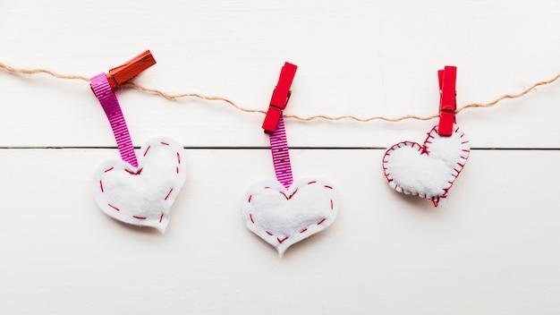 木の板に対して文字列に赤い洗濯はさみで縛らロープの白いステッチハート 無料写真