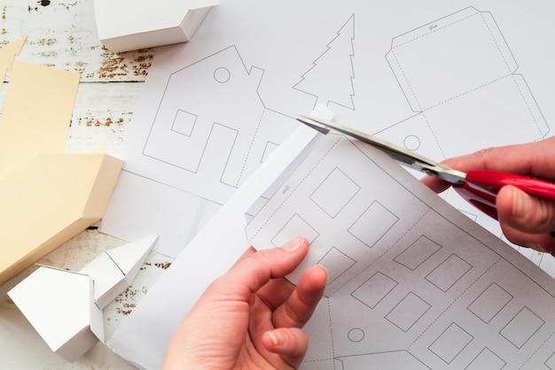 Крупный план руки человека, режущего белую бумагу ножницами Бесплатные Фотографии