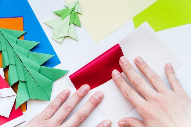 Крупный план руки человека, делающего красочную бумагу на белом фоне Бесплатные Фотографии