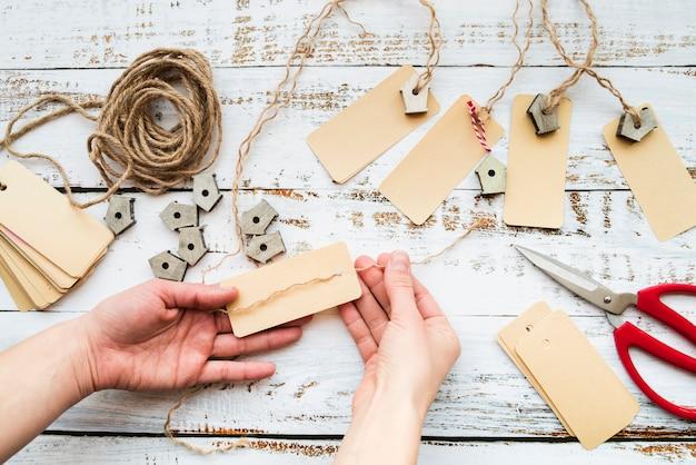 木製のテーブルにタグと巣箱ガーランドを作る人の手のクローズアップ 無料写真