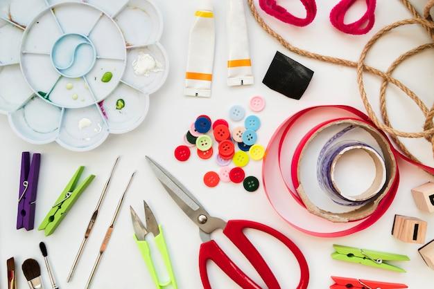 カラーパレット;アクリル塗装チューブ。かぎ針編みボタンリボン;はさみ;洗濯はさみと白い背景で隔離の文字列 無料写真