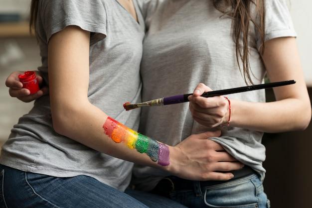 絵筆とアクリル絵の具で若いレズビアンカップルのクローズアップ 無料写真