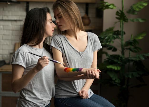 彼女のガールフレンドの手の上にレズビアンの若い女性の絵画レインボーフラグ 無料写真