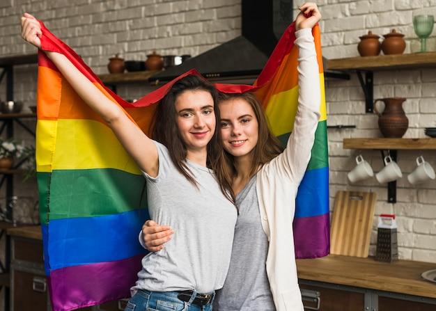 レインボーフラグを手で押し、若いレズビアンカップルの肖像画を笑顔 無料写真
