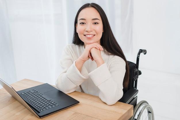木製のテーブルの上のラップトップでカメラを見て車椅子に座っている陽気な障害者の若い女性 無料写真