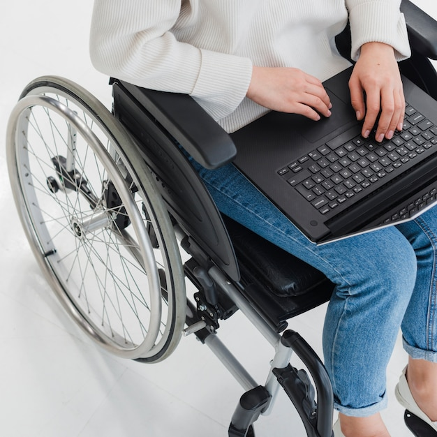 ラップトップを使用して車椅子に座っている女性の側面図 無料写真