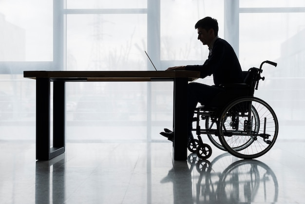 ウィンドウの前にテーブルの上のラップトップを使用して車椅子に座っている実業家のシルエット 無料写真