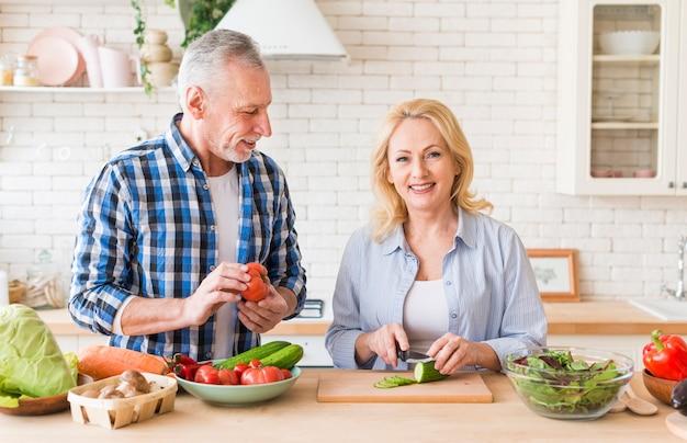 モダンなキッチンで野菜を切る彼女の妻を見ている年配の男性人の肖像画 無料写真
