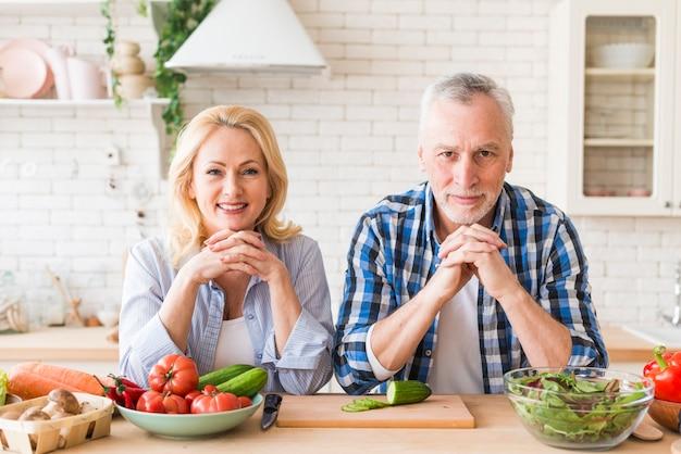 カメラ目線の木製のテーブルにもたれて年配のカップルの肖像画 無料写真