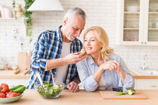 キノコの臭いがする年配の女性が台所で彼女の夫によって保持します。 無料写真