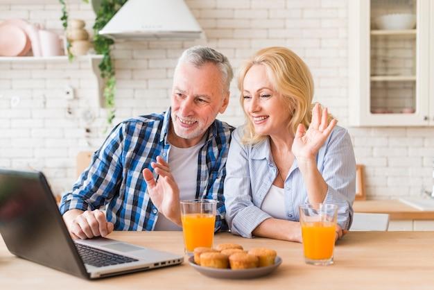 Пожилые супружеские пары, размахивая руками во время онлайн-видео звонок на ноутбуке Бесплатные Фотографии