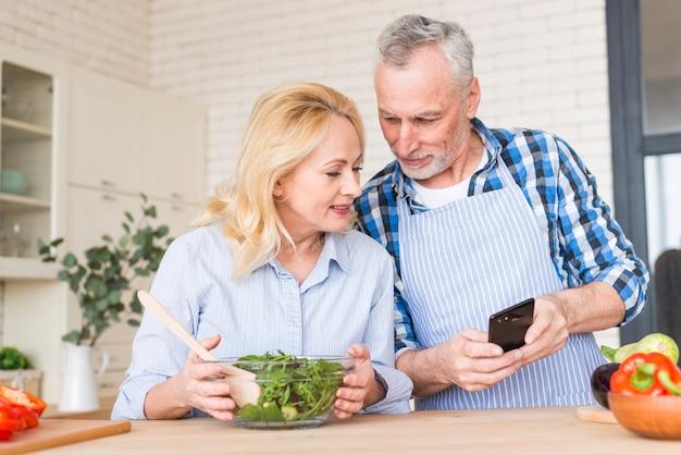 年配の男性が台所で携帯電話で彼の妻に何かを見せて 無料写真
