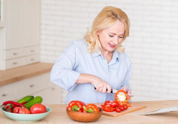 年配の女性が台所でまな板にナイフで赤ピーマンのスライスを切る 無料写真
