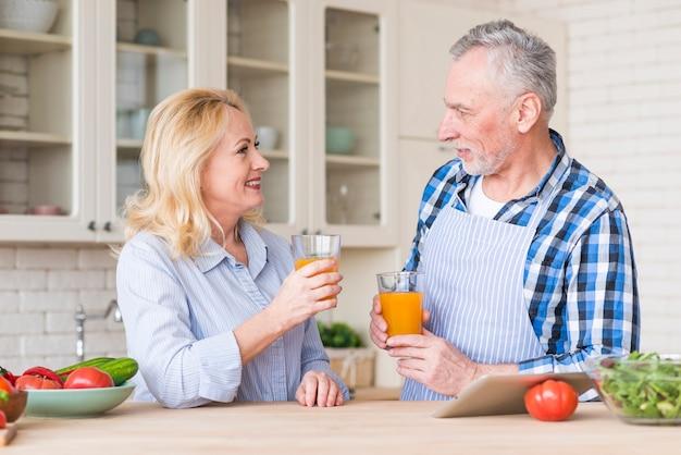 キッチンでお互いを見てジュースのガラスを保持している年配のカップル 無料写真