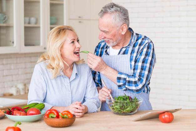 年配の男性が台所で彼女の妻に新鮮なグリーンサラダを供給笑顔 無料写真