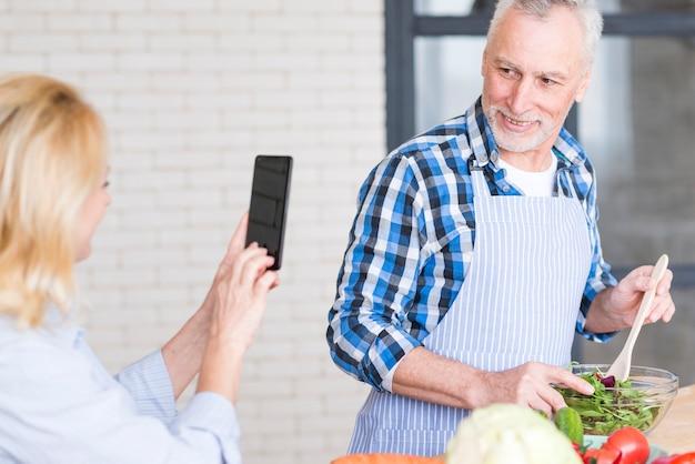 携帯電話でボウルにサラダを準備する彼女の夫の写真を撮る年配の女性のクローズアップ 無料写真