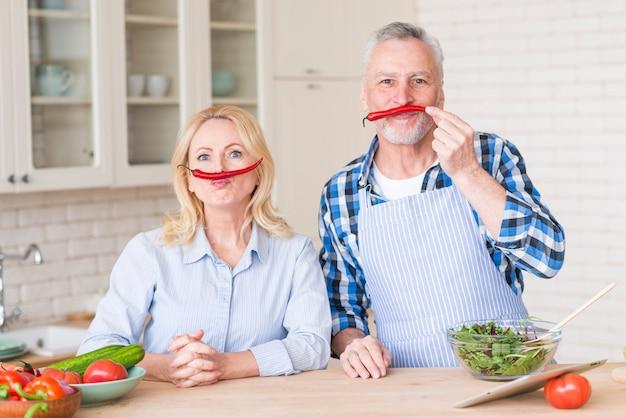 カメラを見て彼らの上唇に赤唐辛子と年配のカップル 無料写真
