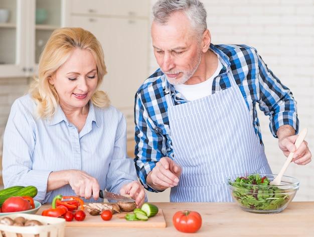 台所でサラダを準備することで彼女の妻を助ける年配の男性人の笑顔 無料写真