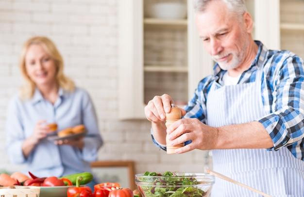 年配の男性人のサラダと台所でバックグラウンドでマフィンを楽しむ彼女の妻 無料写真