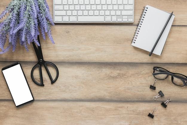 電子機器と机の上のラベンダーの花の近くの文房具 無料写真