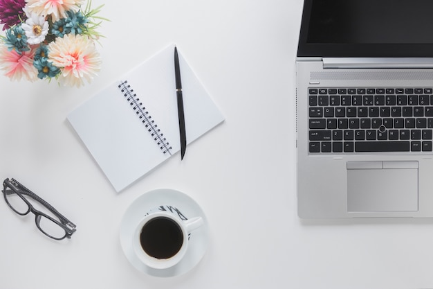 文房具とコーヒーカップの近くのラップトップ 無料写真