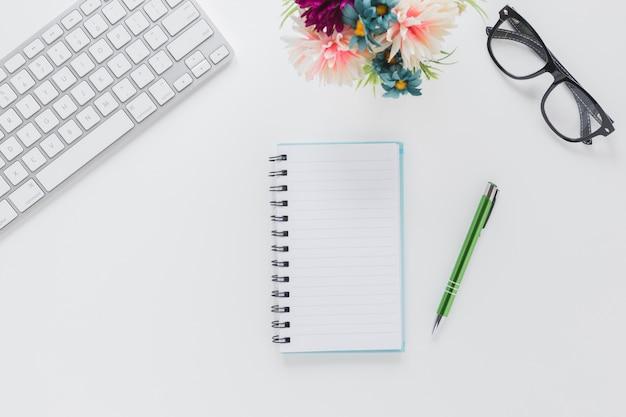 ペンとキーボードと木製のテーブルの花の近くのメガネのノート 無料写真