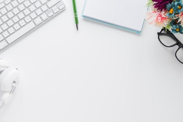 Клавиатура и наушники возле канцелярских принадлежностей и очков Бесплатные Фотографии