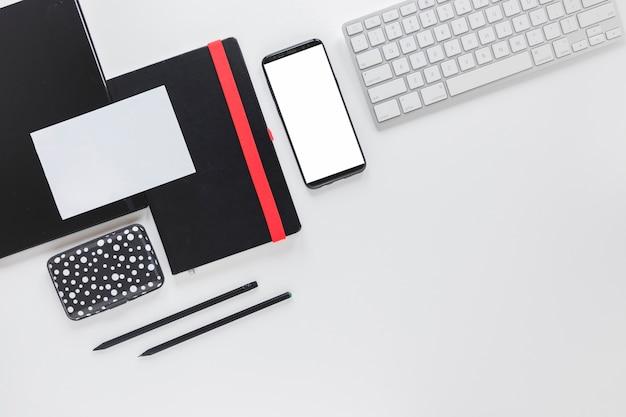 スマートフォンと白いテーブルの上の文房具の近くのキーボード 無料写真