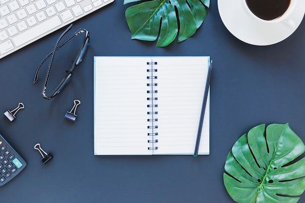 電卓とバインダークリップが付いた濃い青のテーブルの上の文房具、キーボード、メガネの近くのノートブック 無料写真