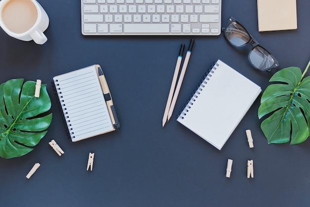 葉を持つテーブルの上のキーボードとコーヒーカップの近くのひな形 無料写真