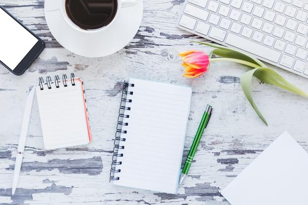 チューリップの花と机の上のスマートフォンとキーボードの近くのノートとコーヒーカップ 無料写真