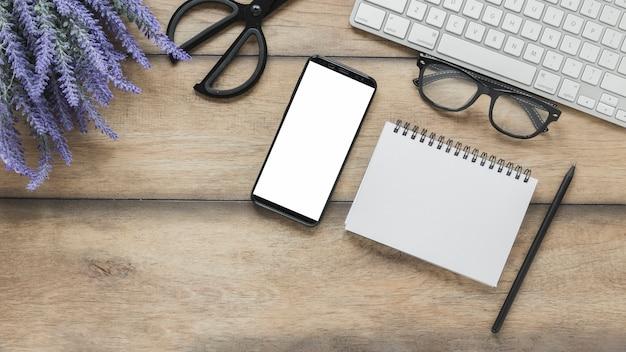 Блокнот и смартфон рядом с цветами лаванды и клавиатурой Бесплатные Фотографии