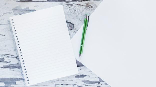 ノートブックと木製のぼろぼろの机の上の紙 無料写真