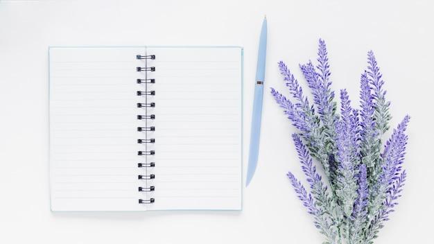 ノートと白い机の上のラベンダーの花の近くのペン 無料写真