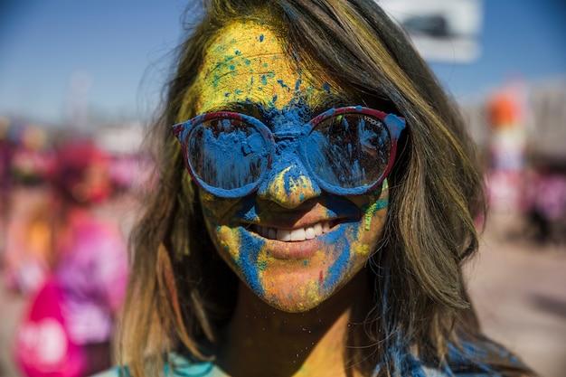 女性の顔に青と黄色のホーリーカラーパウダー 無料写真