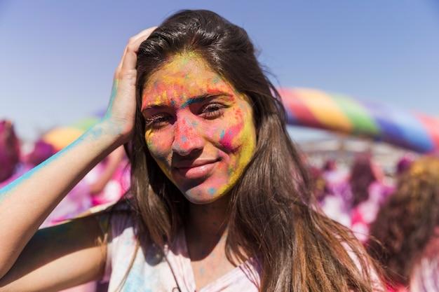 笑顔の若い女性はホーリー色で彼女の顔を覆った 無料写真