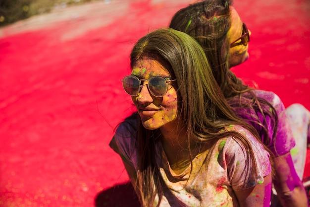 背中合わせに座っているサングラスをかけているホーリーカラーで覆われている若い女性 無料写真
