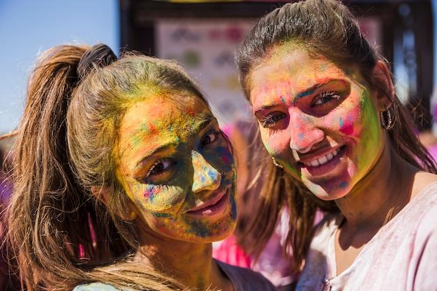 カメラを見て彼らの顔にホーリーカラーを持つ若い女性を笑顔 無料写真