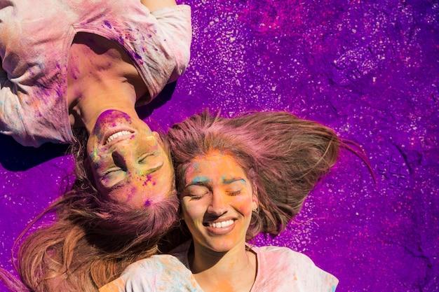 紫色の色の上に横たわるホーリーパウダーで覆われている若い女性 無料写真