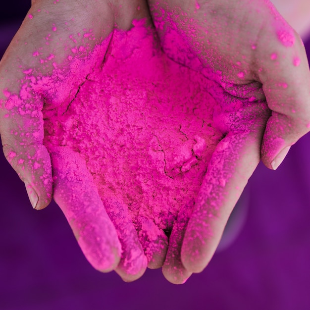 Вид сверху руки человека, держащего розовый цвет холи Бесплатные Фотографии