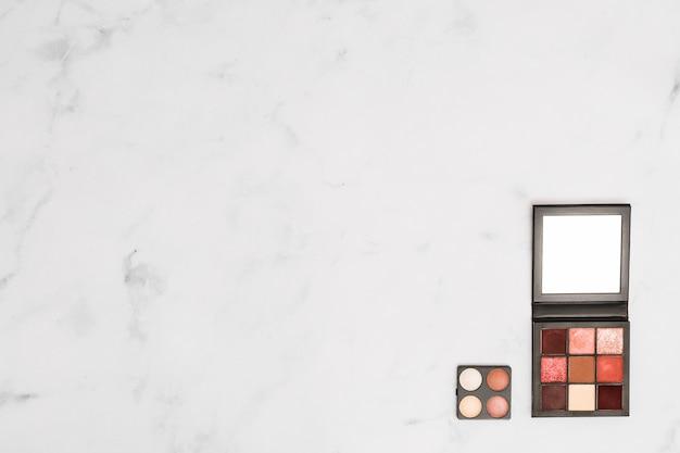 白いテクスチャ背景の隅に化粧品アイシャドウとフェイスパウダーパレット 無料写真