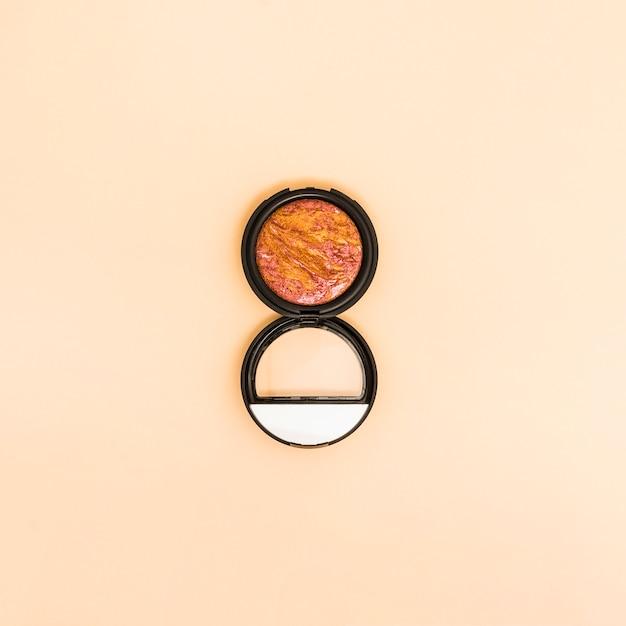 ベージュ色の背景上のコンパクトフェイスパウダー 無料写真